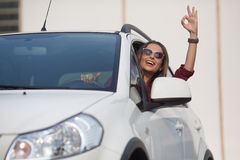 Beautiful lady showing okay sign from her car Royalty Free Stock Images