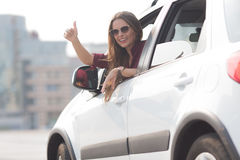 Beautiful lady showing thumb up from her car Stock Image