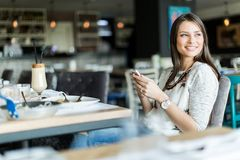 Beautiful lady sitting in a bar and smiling while holding a phon Royalty Free Stock Images