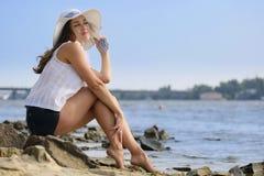 Beautiful lady sitting on the beach royalty free stock image