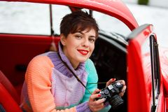 Beautiful lady sitting in car with camera. Female photographer. Travelling concept stock image