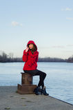 Beautiful lady sitting on the dock beside river on cold autumn d Royalty Free Stock Image