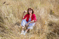 Beautiful lady sitting in high dry summer field to enjoy sun Stock Photography