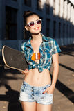 Beautiful lady with skateboard in the city Stock Photography