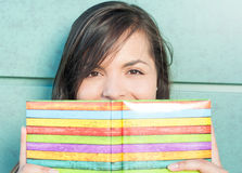 Beautiful lady smiling behind colorful notebook or agenda Royalty Free Stock Photo