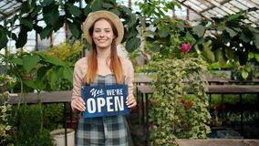 Beautiful lady standing in greenhouse with open sign smiling welcoming buyers. Beautiful young lady wearing hat and apron is standing in greenhouse with we are stock footage