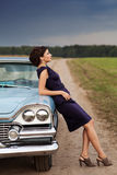 Beautiful lady standing near retro car. Retro woman posing with a retro car outdoors Royalty Free Stock Photos