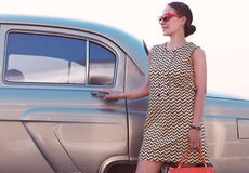 Beautiful lady standing near retro car. Beautiful brunette lady standing near retro car Royalty Free Stock Photography