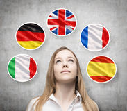 Beautiful lady is surrounded by bubbles with european countries' flags (Italian, German, Great Britain, French, Spanish). Learning of foreign languages concept Stock Photography