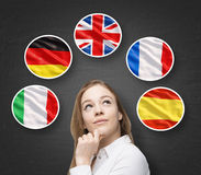 Beautiful lady is surrounded by bubbles with european countries' flags (Italian, German, Great Britain, French, Spanish). Learning. Of foreign languages concept stock image
