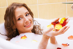 Beautiful lady taking a bath. With rose petals Royalty Free Stock Photography