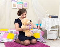 Beautiful lady with teddy bear looking in her hand mirror. In room Royalty Free Stock Image