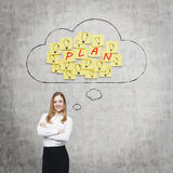 Beautiful lady is thinking about future business plans. Clouds and yellow stickers with the word ' plan '. Beautiful young lady is thinking about future Royalty Free Stock Photo