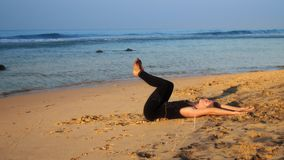 Beautiful lady in tracksuit practices yoga exercise on beach. Beautiful lady in tracksuit practices yoga exercise Rejuvenation on yellow sand beach near blue stock video footage