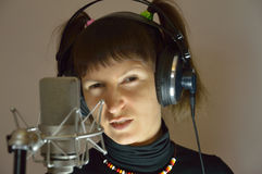 Beautiful lady with two tails near the microphone. The girl in earphones and microphone Royalty Free Stock Photos