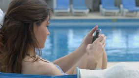 Beautiful lady typing message on smartphone at summer resort. Stock footage stock video footage