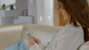 Beautiful lady typing, sending message, texting from smartphone. Stock footage stock footage