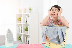 Beautiful lady using iron sort out family clothes. Lovely beautiful lady using iron sort out family clothes feeling bored and leaning on clothing basket thinking Stock Images