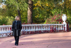 Beautiful lady walking along a stone fence with a white vase. Beautiful lady in a black coat walking along a stone fence with a white vase royalty free stock image