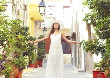 Beautiful lady walking down the street in a white dress. Royalty Free Stock Photo