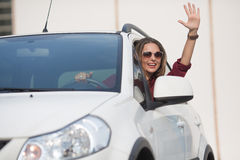 Beautiful lady waving from her car Stock Images