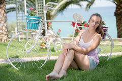 Beautiful lady wear a casual clothes and leaning on a fake decor bicycle Stock Photos
