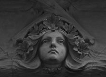 The beautiful lady wears a flower crown. Shot in black and white detail on the sculpture on the facade of this historic building representing some characters / Stock Photography