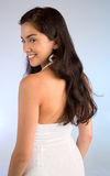 Beautiful Lady in a White Dress Looking Back. A beautiful young lady in a white dress looking back at the camera Royalty Free Stock Photos