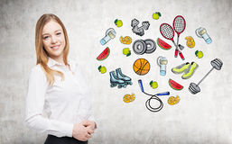 A beautiful lady who is trying to make a choice in favour of a certain sport activity. Colourful sport icons are drawn on the conc Royalty Free Stock Images