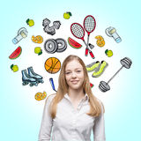 A beautiful lady who is trying to make a choice in favour of a certain sport activity. Colourful sport icons are drawn on the ligh. T blue background. A concept Stock Photography