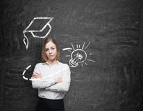 Beautiful Lady With Crossed Hands Is Thinking About Education. A Graduation Hat And A Light Bulb Are Drawn On The Chalkboard Royalty Free Stock Images