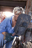 Beautiful lady at work in his old workshop. Beautiful lady dressed in overalls at work in his old workshop Royalty Free Stock Image