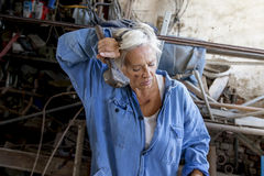 Beautiful lady at work in his old workshop. Beautiful lady dressed in overalls at work in his old workshop Royalty Free Stock Photography