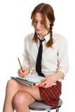 Beautiful lady writing on a worksheet. White background Stock Photos