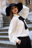 Beautiful ladylike woman in elegant blouse and felt hat Stock Image