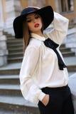 Beautiful ladylike woman in elegant blouse and felt hat Stock Image