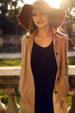 Beautiful ladylike woman in elegant fashion clothes posing at park Stock Image