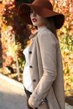 Beautiful ladylike woman wearing elegant clothes posing in park Royalty Free Stock Image