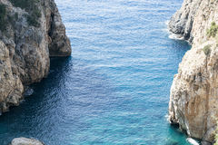 Beautiful lagoon with rocks descending to sea Stock Images