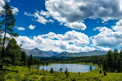 Beautiful lake in the Altai mountains, Siberia, Russia. Wild mountain lake on the background of snowy peaks. Summer landscape. In the mountains royalty free stock image