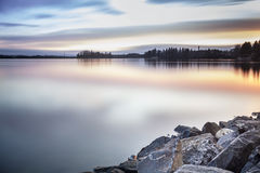 Beautiful lake coast during sunrise Stock Photos