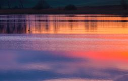 Beautiful lake with colorful sunset sky reflected in water. Tranquil vibrant landscape Royalty Free Stock Photos