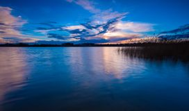 Beautiful lake with colorful sunset sky. Tranquil vibrant landscape Stock Image