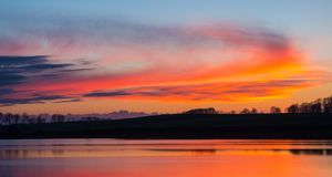 Beautiful lake with colorful sunset sky. Tranquil vibrant landscape Royalty Free Stock Photo