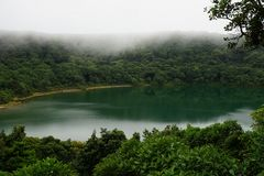 Beautiful lake in the crater of a volcano surrounded with tropical cloud forest, Costa Rica. Royalty Free Stock Images