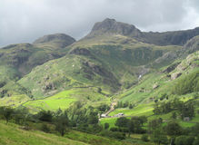 Great Langdale Valley, Cumbria. Sun lights up a brooding Great Langdale Valley in the Cumbrian Lake District in England. With a stunning backdrop of the famous Stock Photo