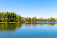 Beautiful lake with forest reflection on sunny spring day.