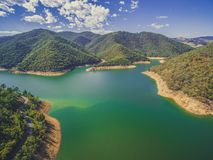 Lake among forested hills. Beautiful lake among forested hills on bright sunny day Stock Photos