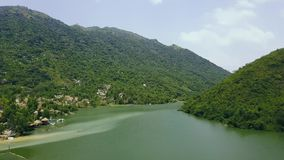 Beautiful lake in green mountains covered tropical forest aerial footage. Natural landscape river and high green. Mountain from flying drone stock video footage