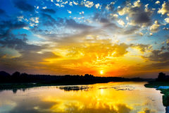 Beautiful lake landscape with vivid sunrise on the cloudy sky Stock Photos